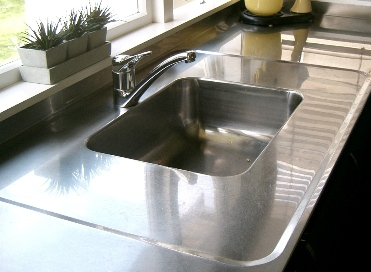 Polished stainless steel bench top with welded sink and anti spill border